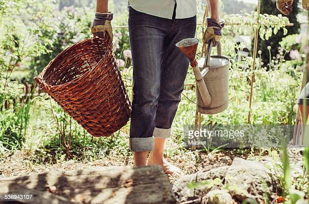 Midsection of man carrying wicker basket and watering can at yard