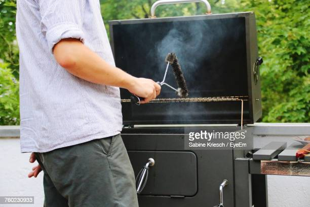 Midsection Of Man Cleaning Barbecue Grill With Wire Brush