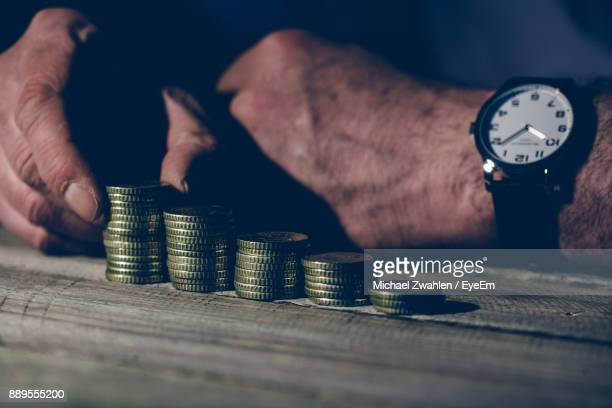 Midsection Of Man Counting Coins On Wooden Table