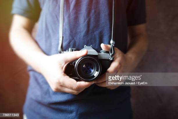 Midsection Of Man Holding Digital Camera Against Wall