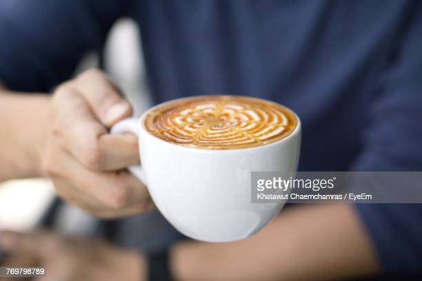 Midsection Of Man Holding Froth Art On Coffee In Cup