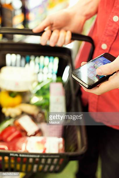 Midsection of man holding mobile phone while carrying grocery basket in supermarket