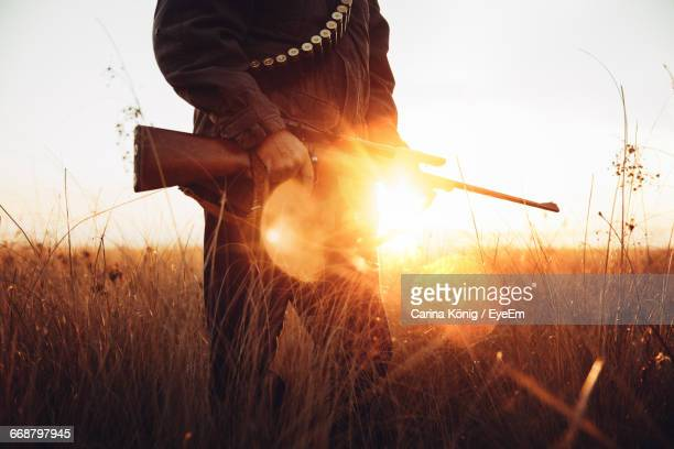 Midsection Of Man Holding Rifle On Field Against Sky During Sunset