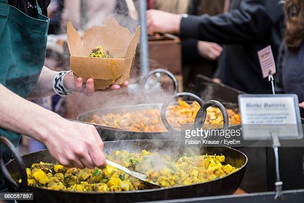 Midsection Of Man Packing Food At Market Stall