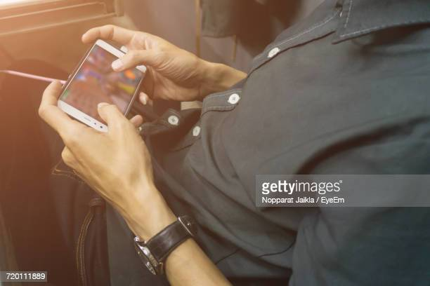 Midsection Of Man Playing Games In Mobile Phone