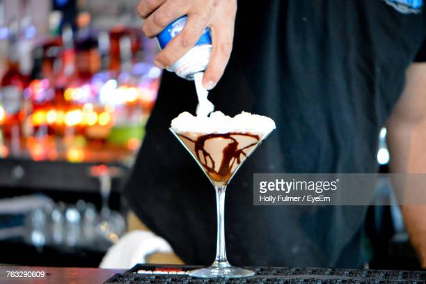 Midsection Of Man Preparing Drink On Table