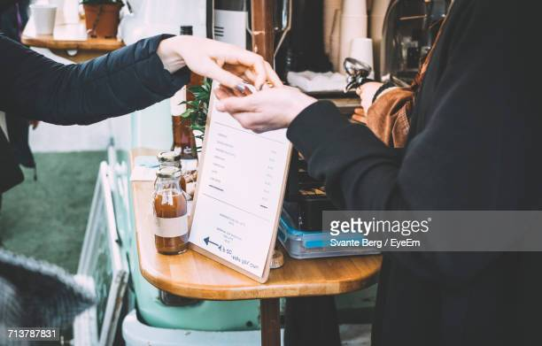 Midsection Of Man Receiving Money In Store