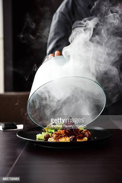 Midsection Of Man Serving Food On Table