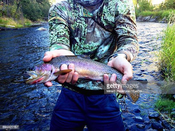 Midsection Of Man Showing Fish While Standing Against River