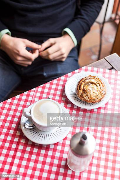 Midsection of man sitting at cafe table