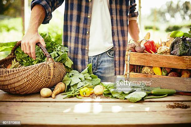 Midsection of man standing with vegetables at table