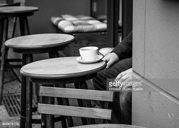 Midsection Of Man With Cigarette And Coffee At Sidewalk Cafe