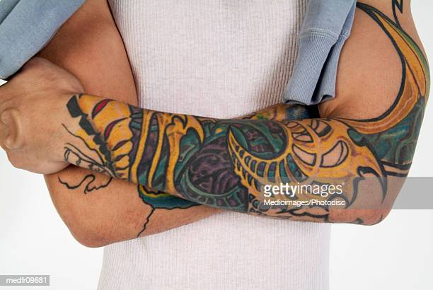 Midsection of man with tattooed arms, close-up