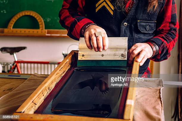 Midsection of mature male worker using squeegee to pull ink across stencil on screen at workshop