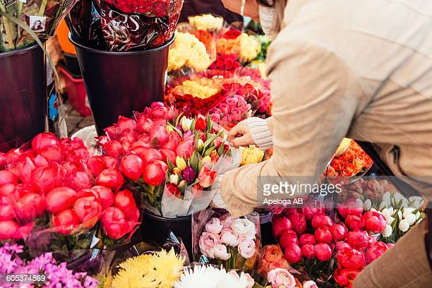 Midsection of mature woman buying flowers at market stall