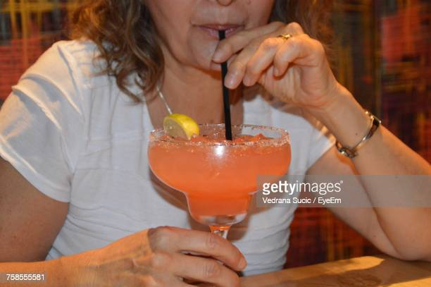 Midsection Of Mature Woman Having Drink At Table