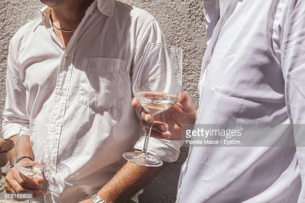 Midsection Of Men Holding Wineglasses At Wedding Party