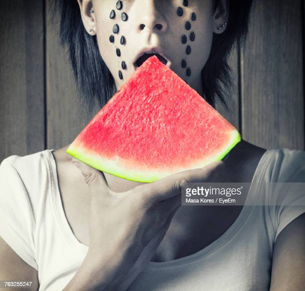Midsection Of Mid Adult Woman Eating Watermelon Against Wooden Wall
