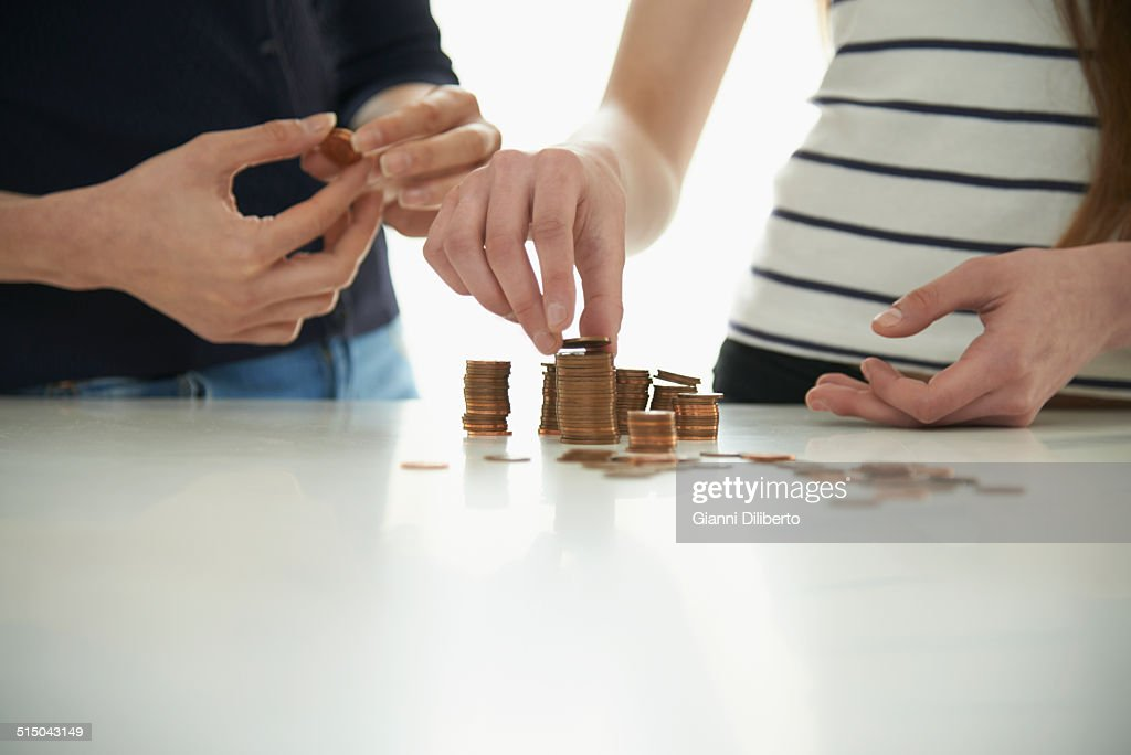 Midsection of mother and daughter stacking coins at table