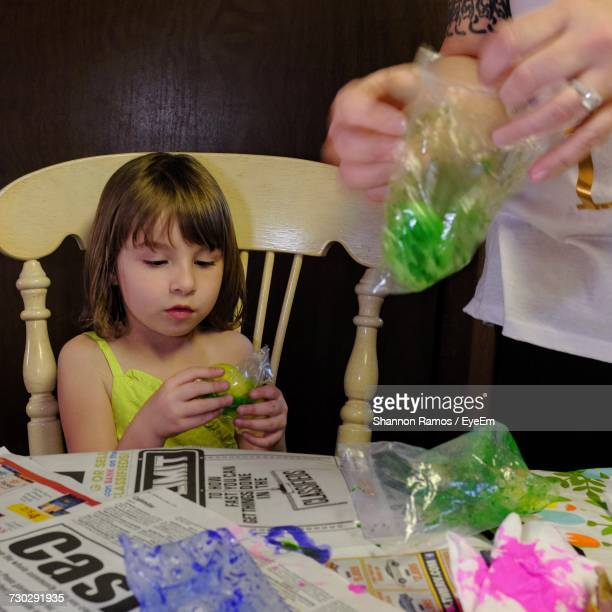 Midsection Of Mother By Daughter Opening Packet At Home During Easter