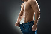 Midsection of muscular man in old jeans showing weight loss against black background