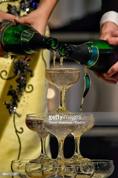 Midsection Of People Pouring Champagne In Stacked Glasses