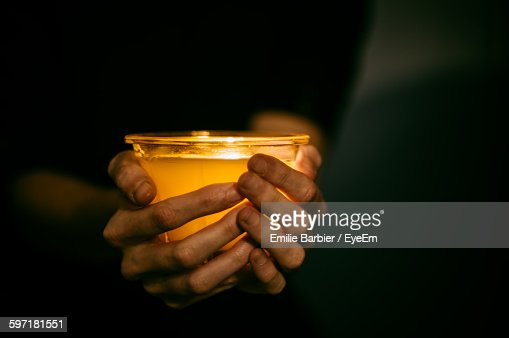 Midsection Of Person Holding Tea Light Candle In Darkroom