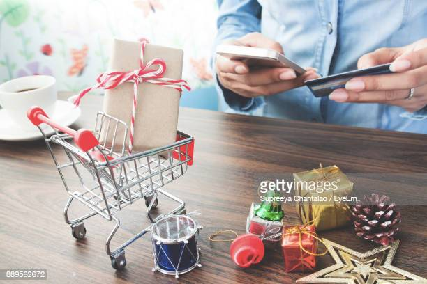 Midsection Of Person Online Shopping With Christmas Decorations On Table