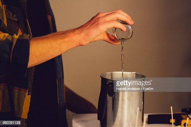 Midsection Of Person Pouring Liquid Wax In Pitcher