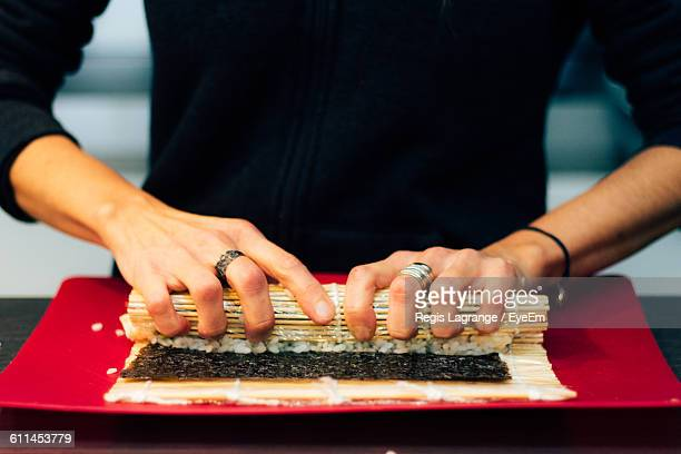 Midsection Of Person Rolling Sushi In Plate