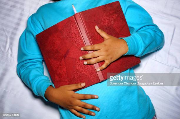 Midsection Of Person With Book On Bed