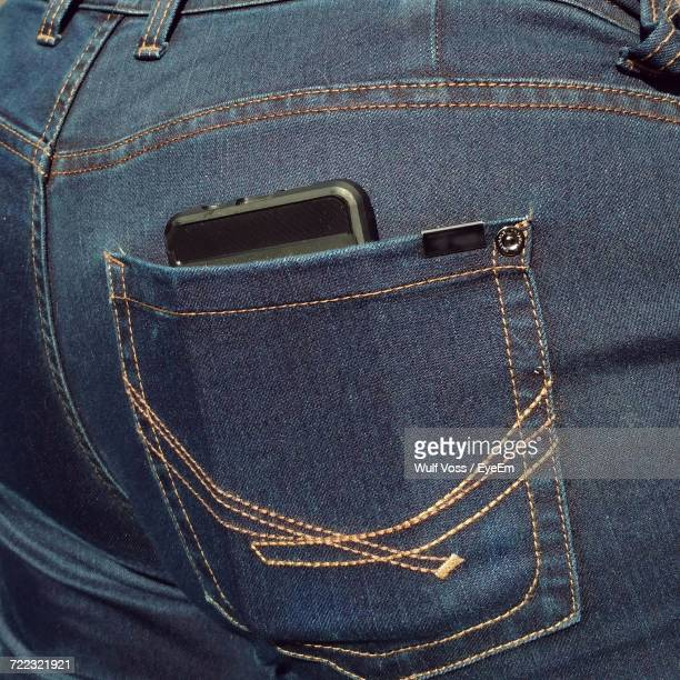 Midsection Of Person With Mobile Phone In Back Pocket