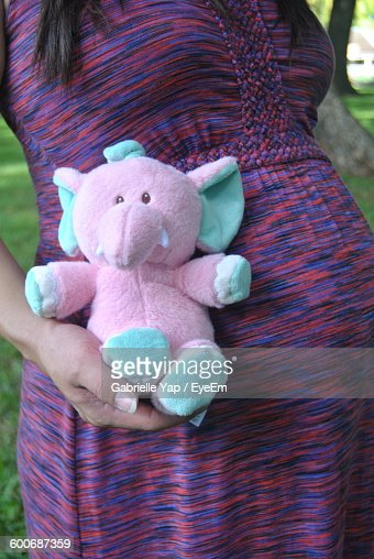 Midsection Of Pregnant Woman Holding Elephant Toy