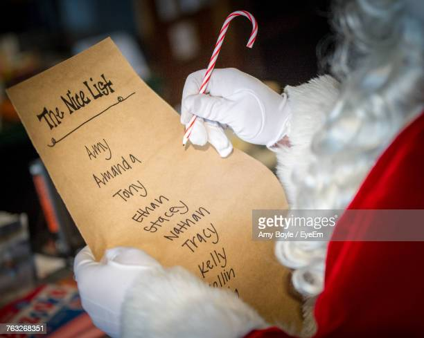 Midsection Of Santa Claus Writing On Paper