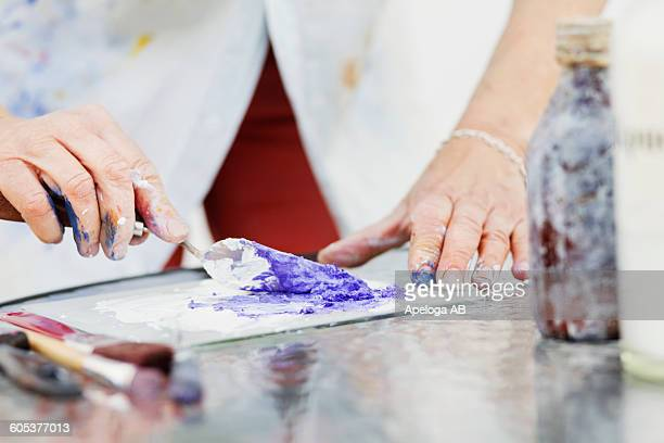 Midsection of senior female artist mixing paint in studio