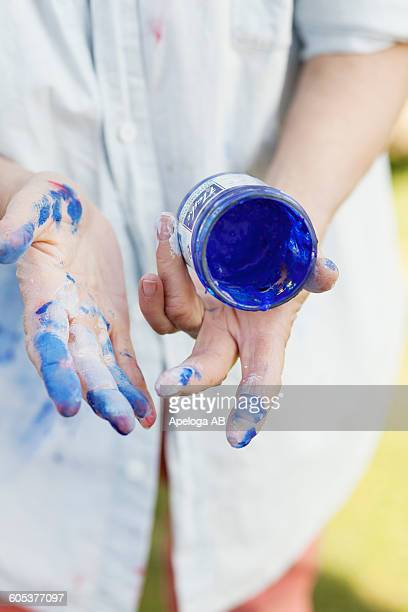 Midsection of senior female painter with messy hands holding blue paint can outdoors