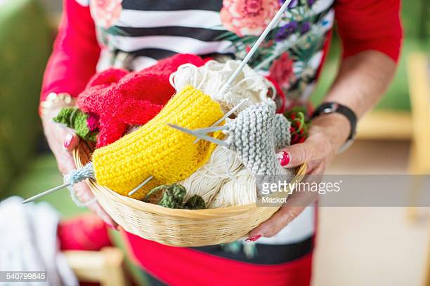 Midsection of senior woman holding knitting basket at nursing home