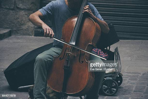 Midsection Of Street Musician Playing Cello On Footpath