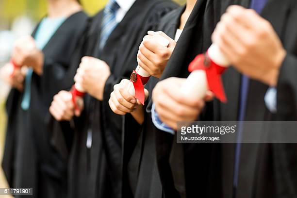 Midsection Of Students Holding Certificates On Graduation Day