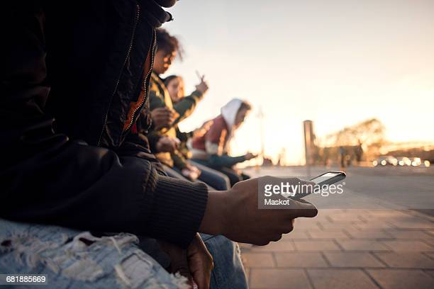 Midsection of teenager using phone while sitting with friends by cobbled street