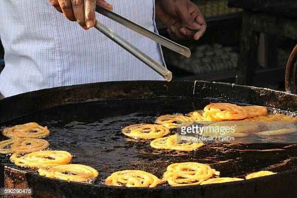 Midsection Of Vendor Frying Jalebis At Store