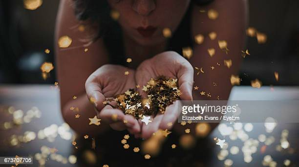 Midsection Of Woman Blowing Star Shape Confetti