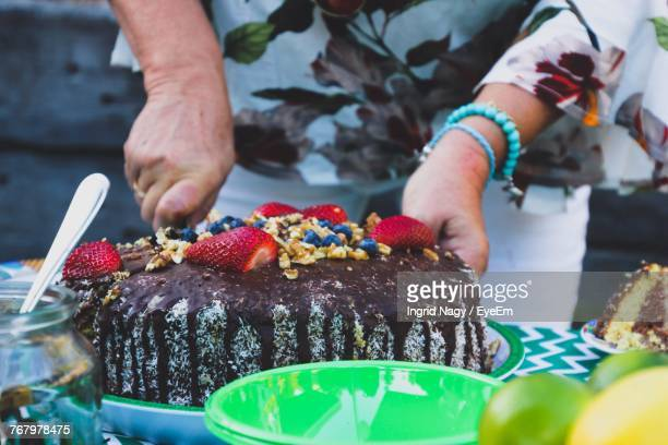 Midsection Of Woman Cutting Cake On Table