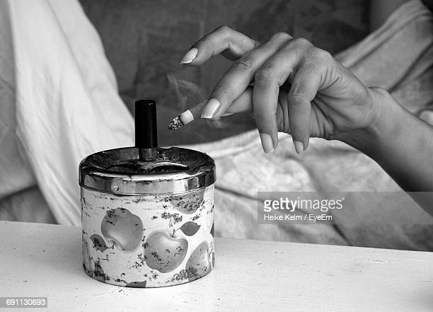 Midsection Of Woman Flicking Cigarette In Ashtray While Resting At Home