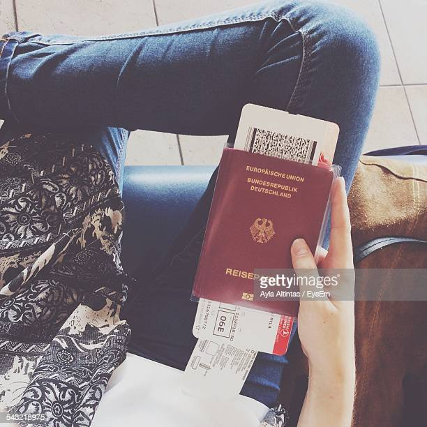 Midsection Of Woman Holding Airplane Ticket And Passport In Airport