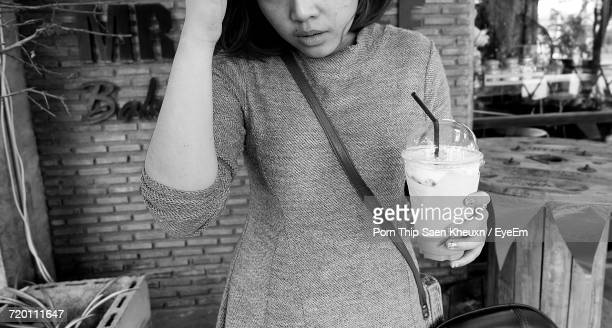 Midsection Of Woman Holding Coffee Against Brick Wall