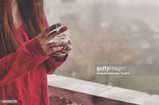 Midsection Of Woman Holding Coffee Cup And Cigarette