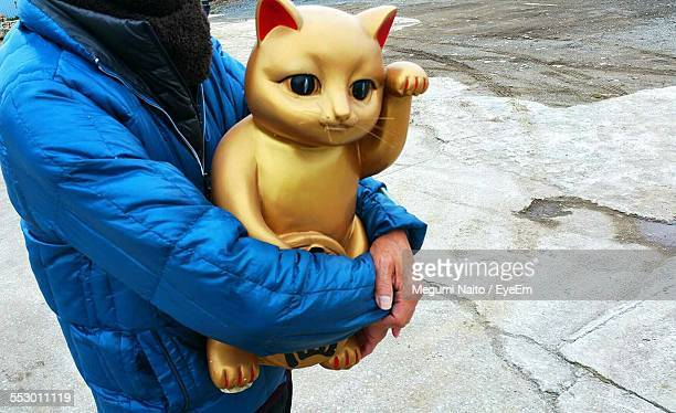 Midsection Of Woman Holding Lucky Cat Figurine