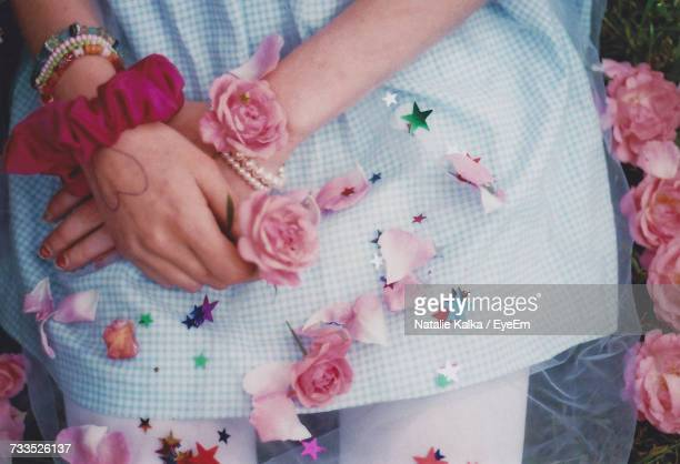 Midsection Of Woman Holding Pink Rose On Field