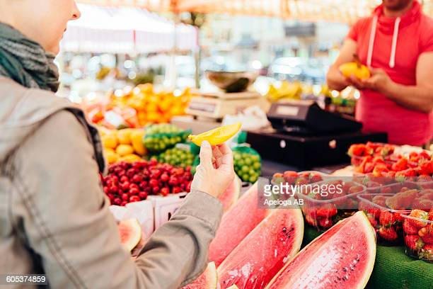 Midsection of woman holding slice of mango at fruit stall